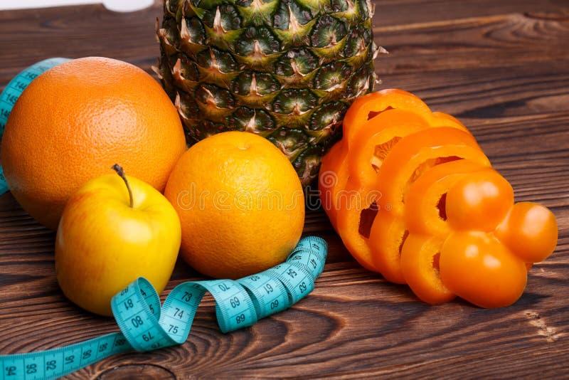 Konditionbegrepp med ananas, apelsiner, äpplen, söt peppar och mätaband royaltyfri foto