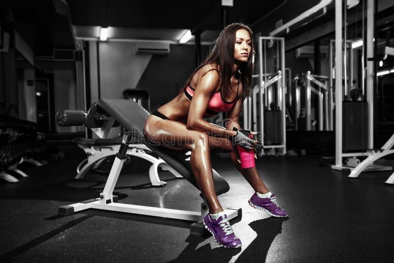 Konditionflicka med shaker som poserar på bänk i idrottshallen royaltyfri foto