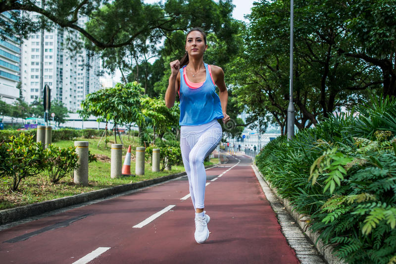Konditionflicka som joggar på den rinnande banan i parkera i sommar royaltyfri fotografi