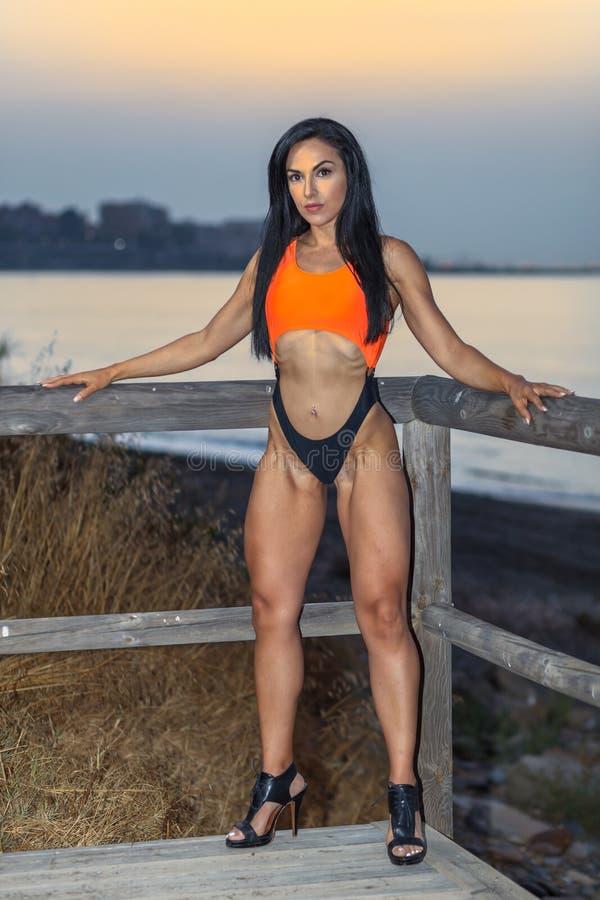 Konditionflicka som poserar med en härlig svart och orange bikini royaltyfri fotografi