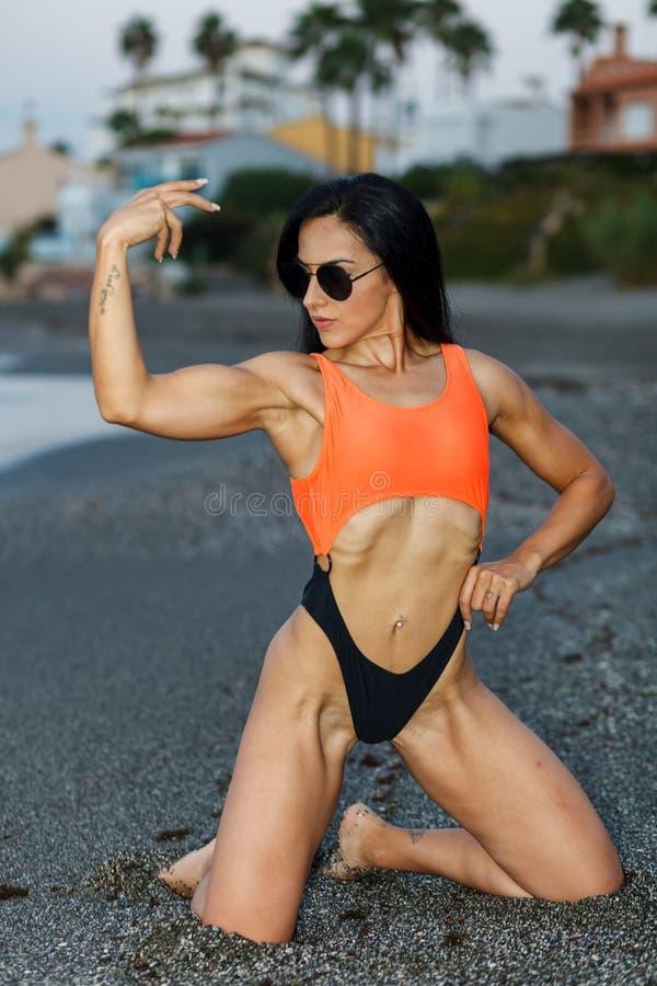 Konditionflicka som poserar med en h?rlig svart och orange bikini arkivbild