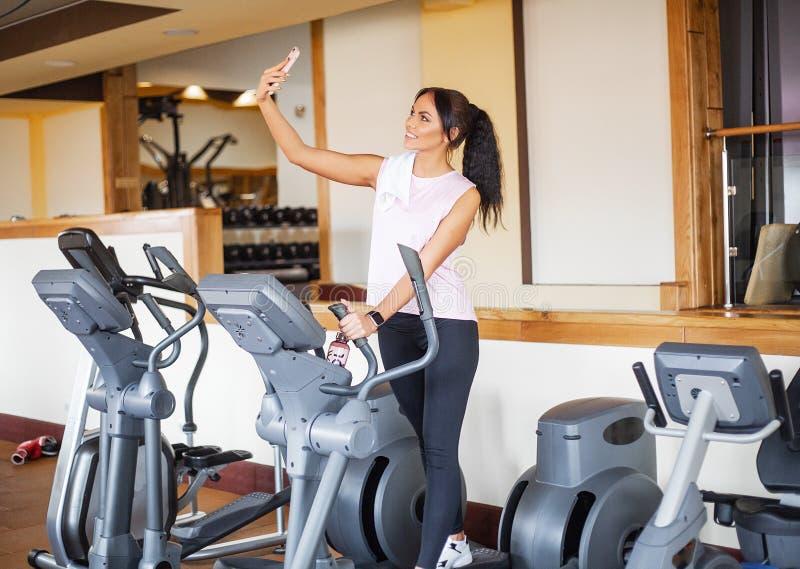 Konditionflickagenomkörare i idrottshallen Övningar för kvinnor, kroppsbyggaredrev, sportlivsstil arkivbilder