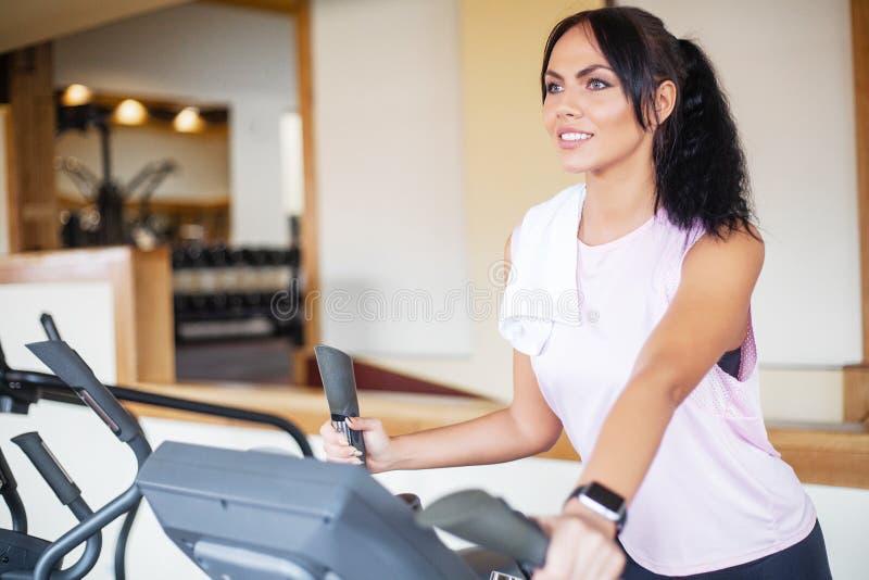 Konditionflickagenomkörare i idrottshallen Övningar för kvinnor, kroppsbyggaredrev, sportlivsstil royaltyfri bild