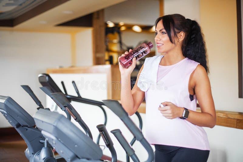 Konditionflickagenomkörare i idrottshallen Övningar för kvinnor, kroppsbyggaredrev, sportlivsstil royaltyfria bilder