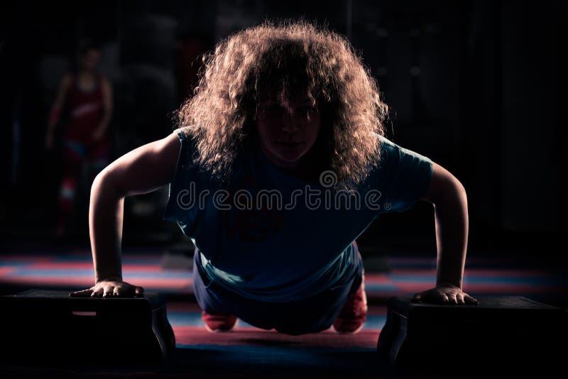 Konditionflickan utarbetar med gradvist Stark brunett med lockigt hår som gör aerobics på gradvist Stark ung flicka som övar på royaltyfria bilder