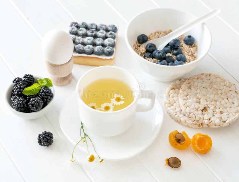 Konditionfrukost: granola med bär och frukter, ägg och te royaltyfri fotografi