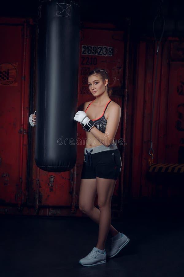 Konditiongrupp Bärande handskar för ung härlig sportkvinna som poserar på bakgrunden av boxningidrottshallen arkivfoto