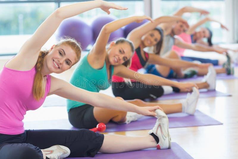 Konditiongrupp och instruktör som gör sträcka övning på yogamats royaltyfria bilder