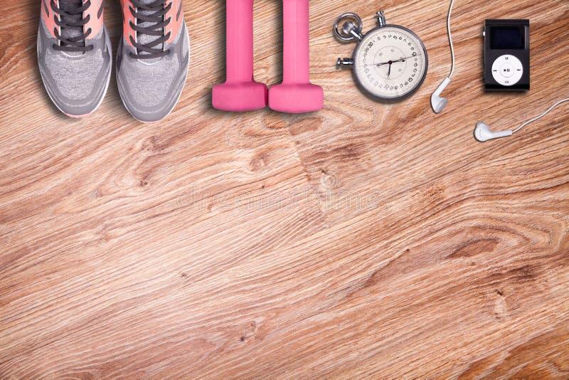 Konditionidrottshall och rinnande utrustning Hantlar och rinnande skor, parallell stoppur och musikspelare arkivfoto