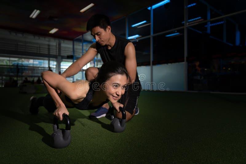 Konditioninstruktör med flickan på utbildning i konditionmitten, skott av den unga kvinnan som gör push-UPS på idrottshallen Musk royaltyfria bilder