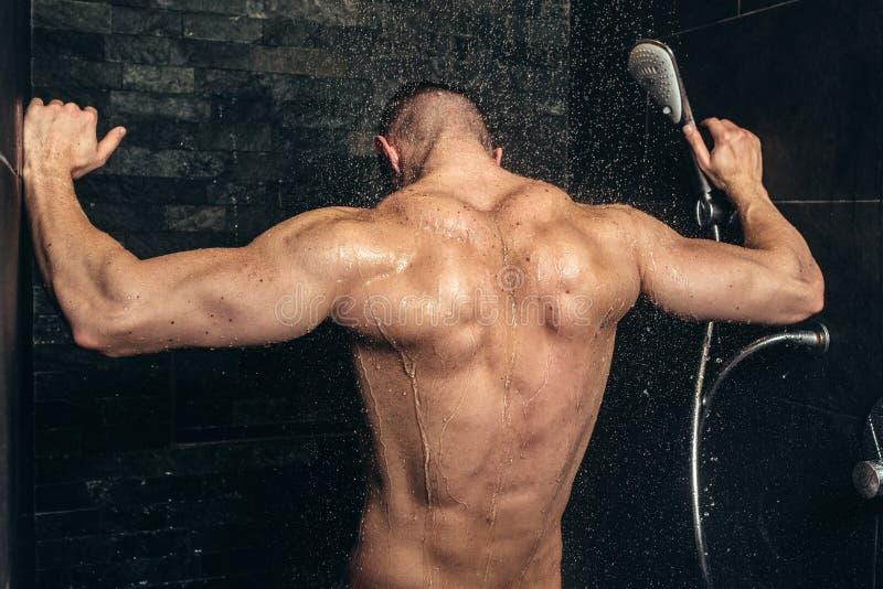 Konditionkroppsbyggare som tar en dusch, når utbildning För slut detaljer upp av tillbaka muskler i dusch arkivfoton