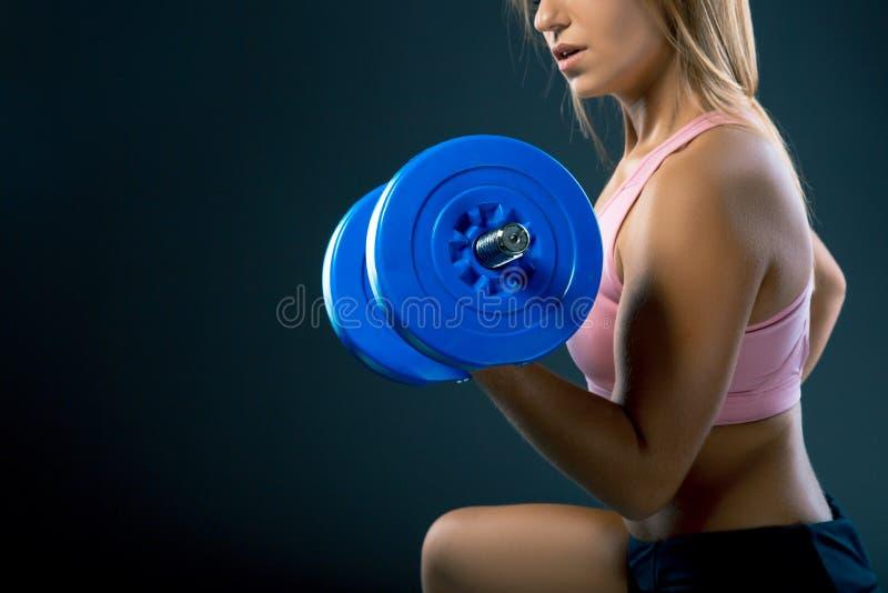 Konditionkroppsbyggarekvinna med hantlar blond flicka för skönhet med muskler i idrottshall royaltyfria bilder