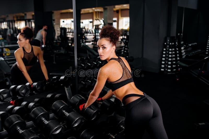 Konditionkvinna i idrottshallen Sportgenomkörareövningar med dumbbels royaltyfri foto