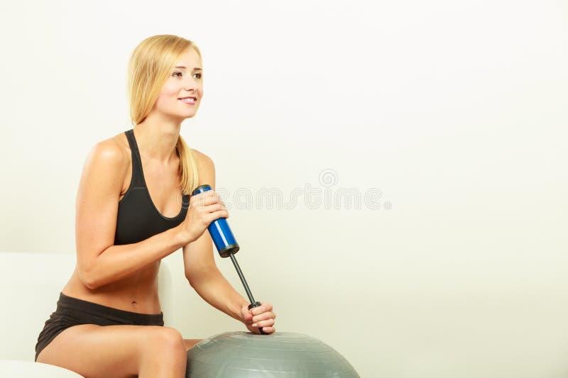Konditionkvinna med luftpumpen som blåser upp passformbollen arkivfoton