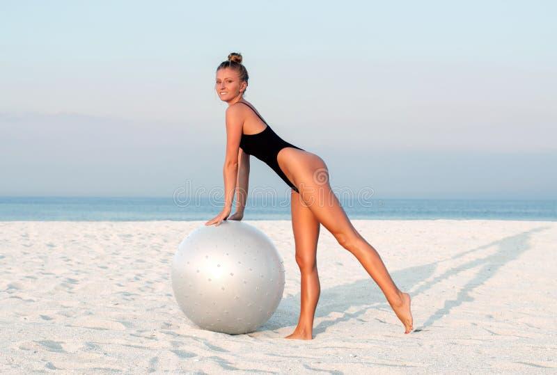 Konditionkvinna med passformbollen på stranden utomhus arkivfoton