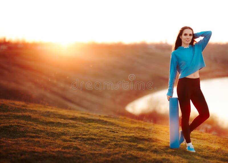 Konditionkvinna med yoga som är matt i natur på solnedgången arkivfoto