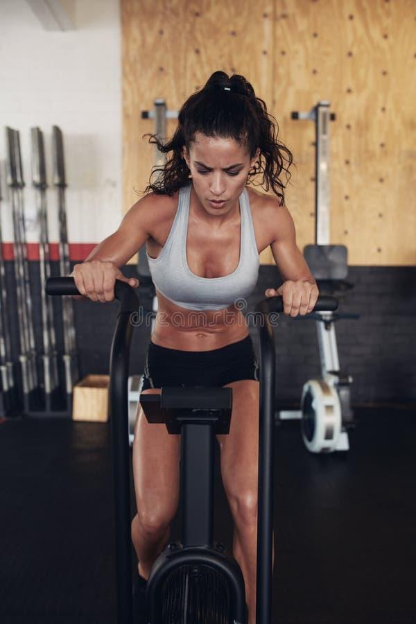 Konditionkvinna på cykeln som gör cardio genomkörare på idrottshallen royaltyfria bilder