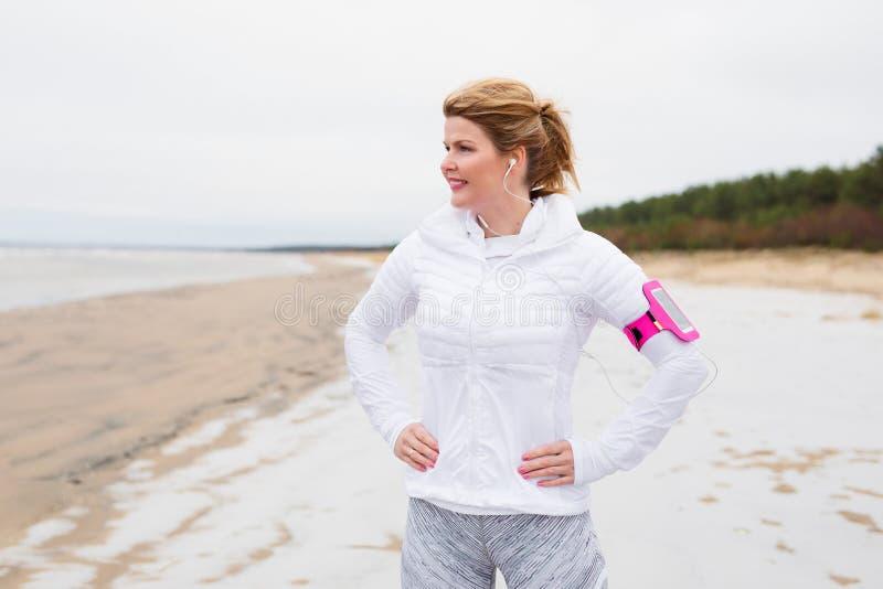Konditionkvinna på stranden i vinter royaltyfri bild