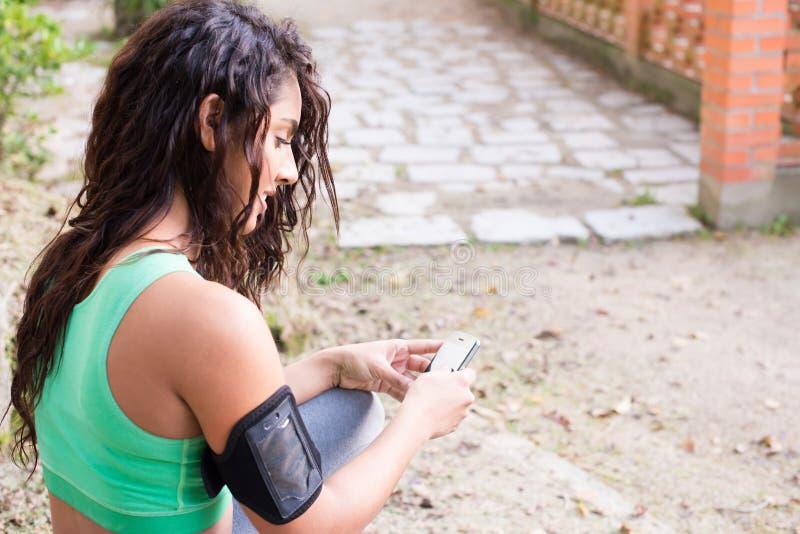 Konditionkvinna som använder telefonen arkivfoton