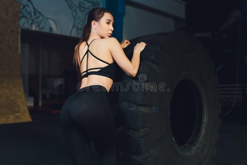 Konditionkvinna som bl?ddrar hjulgummihjulet i idrottshall F?rdig kvinnlig idrottsman nen som utarbetar med ett enormt gummihjul  royaltyfria bilder