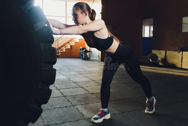 Konditionkvinna som bl?ddrar hjulgummihjulet i idrottshall F?rdig kvinnlig idrottsman nen som utarbetar med ett enormt gummihjul  arkivbilder