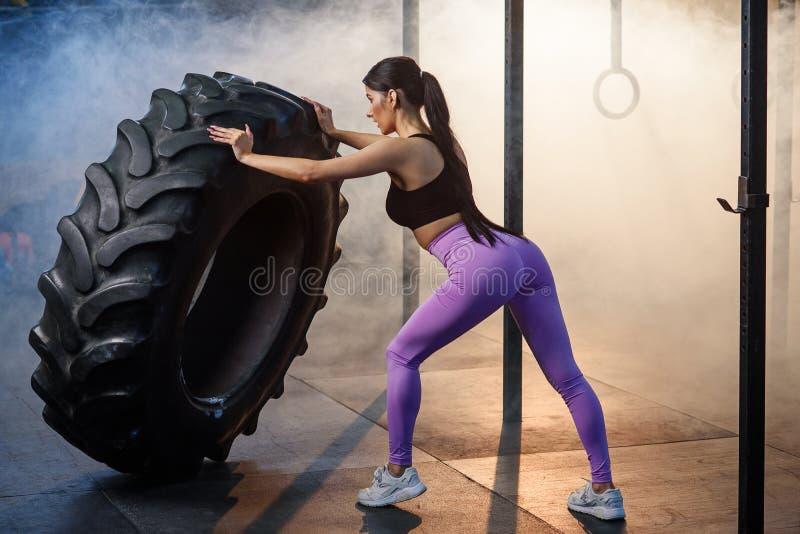 Konditionkvinna som bl?ddrar hjulgummihjulet i idrottshall arkivfoto