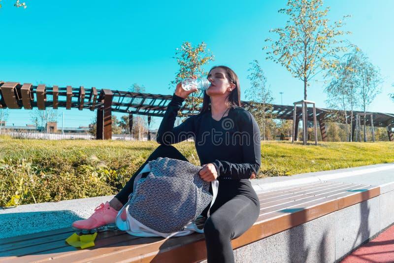 Konditionkvinna som dricker buteljerat vatten, når att ha övat utomhus arkivfoton