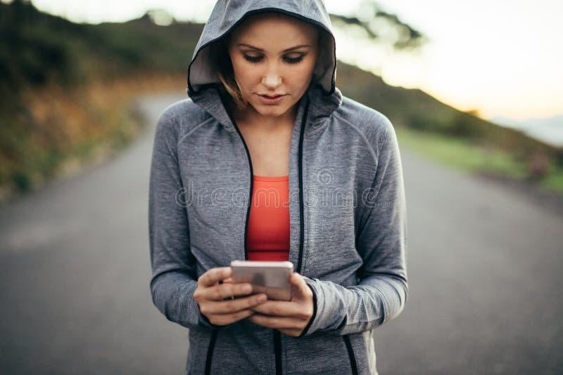 Konditionkvinna som går på gatan som bär en med huva svettas skjorta som ser hennes mobiltelefon Kvinna som använder hennes mobil fotografering för bildbyråer