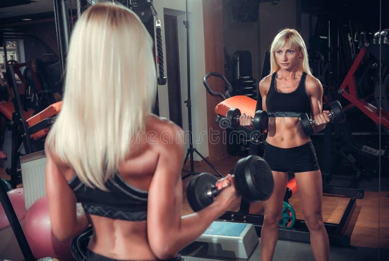Konditionkvinna som gör övningar med hanteln i idrottshallen arkivfoton