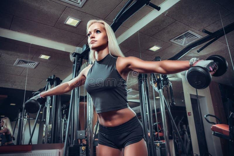 Konditionkvinna som gör övningar med hanteln i idrottshallen royaltyfri bild