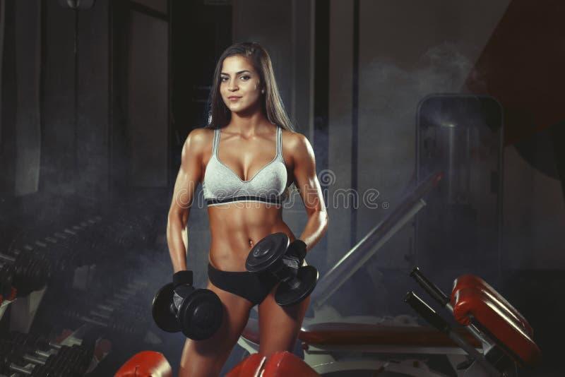 Konditionkvinna som gör en konditiongenomkörare med hantlar i idrottshallen arkivbild