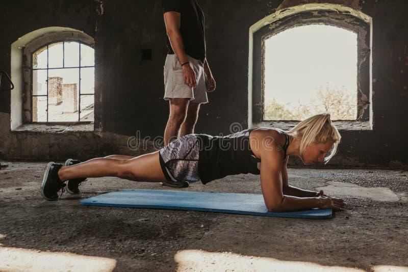 Konditionkvinna som gör plankan medan instruktör som står bredvid henne arkivbilder