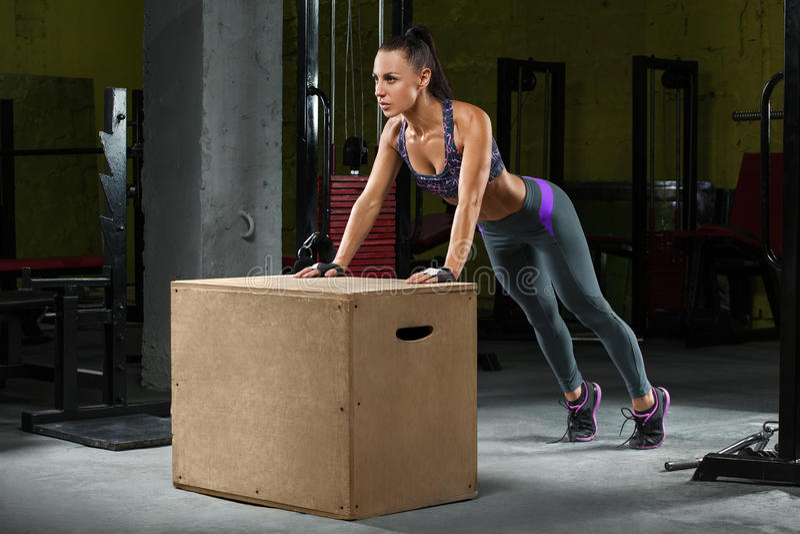 Konditionkvinna som gör push-UPS på crossfitasken i idrottshall Idrotts- flickagenomkörare fotografering för bildbyråer