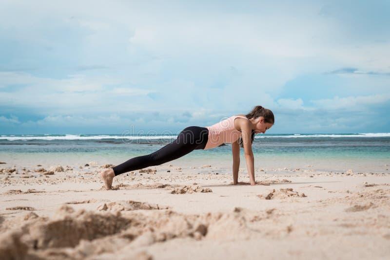 Konditionkvinna som gör yogaövningar Flickan som utbildar hennes abs som övar kärna, tränga sig in med plankan poserar arkivbild