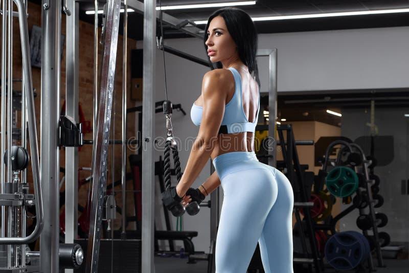 Konditionkvinna som g?r ?vningen f?r triceps H?rliga bakdelar i damasker Sexig idrotts- flickagenomk?rare i idrottshall royaltyfri foto