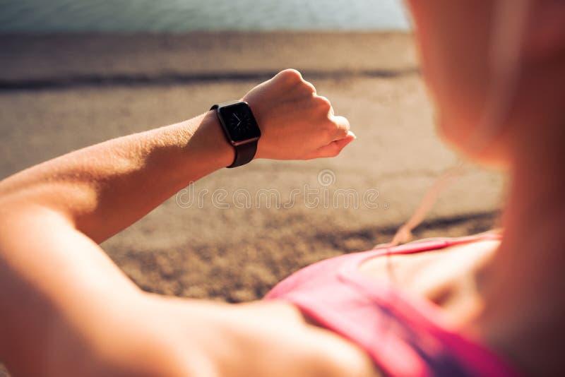 Konditionkvinna som kontrollerar tid på smartwatch royaltyfri bild