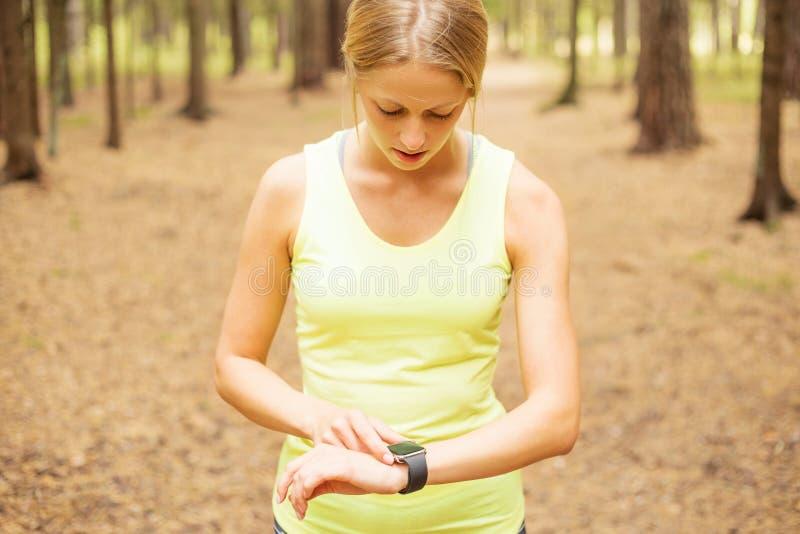 Konditionkvinna som ser smartwatch royaltyfri bild