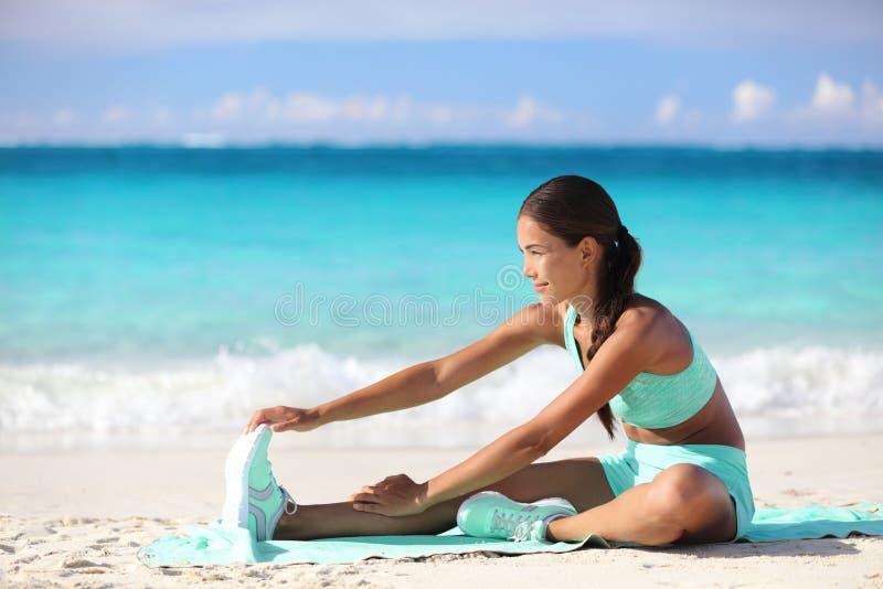 Konditionkvinna som sträcker ben på stranden - sportig asiatisk flicka som gör benelasticitet arkivfoto