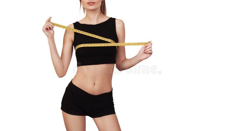 Konditionkvinna som upp mäter hennes bröstkorg som isoleras på vit slank huvuddel Flicka med måttbandet kopiera avstånd Kondition royaltyfri foto