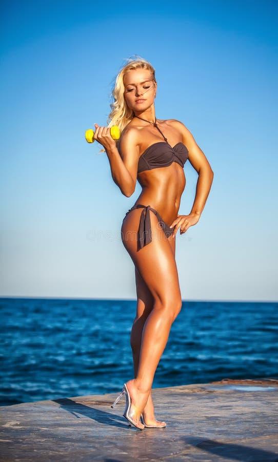 Konditionkvinna som utarbetar på stranden i sommar royaltyfri foto