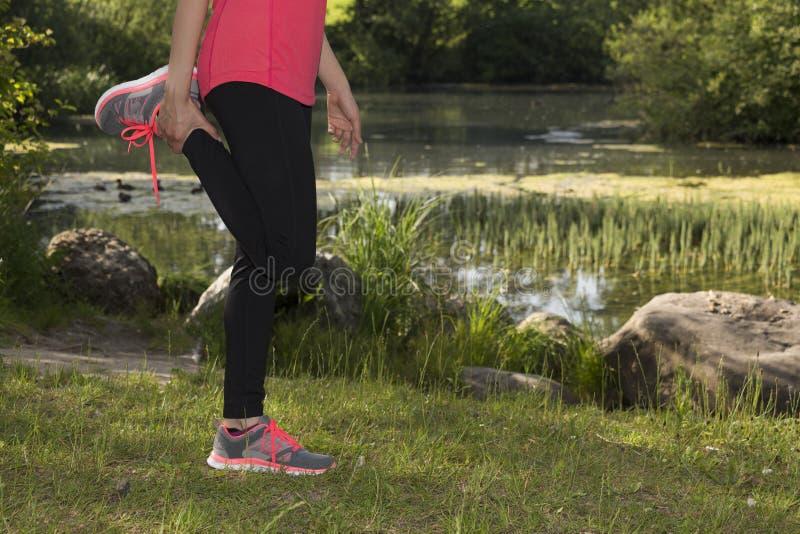 Konditionkvinna som utomhus sträcker henne ben under sportar arkivbild