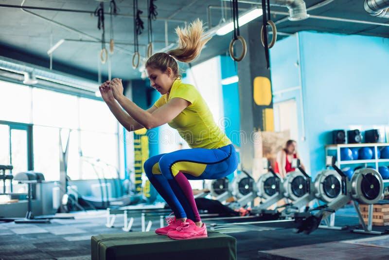 Konditionkvinnabanhoppning på askutbildning på idrottshallen, flickan i leggins och enskjorta arkivfoto