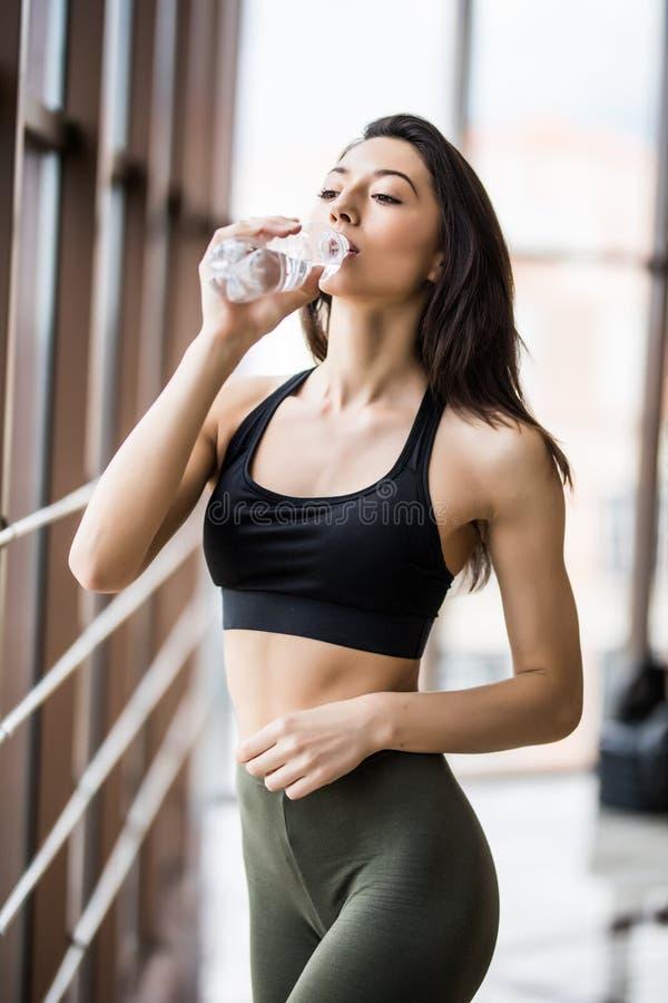 Konditionkvinnadricksvatten från flaskan Muskulös ung kvinnlig på idrottshallen som tar ett avbrott efter genomkörare fotografering för bildbyråer