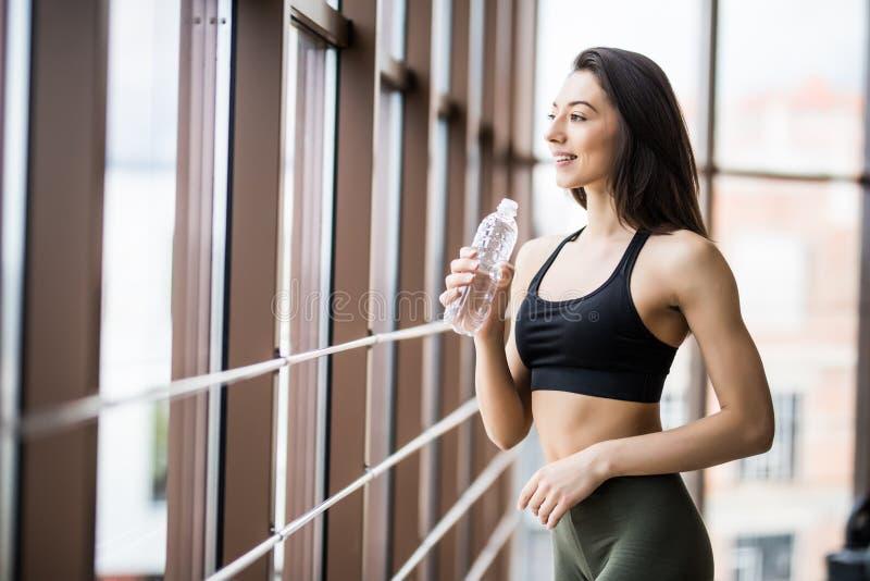 Konditionkvinnadricksvatten från flaskan Muskulös ung kvinnlig på idrottshallen som tar ett avbrott efter genomkörare arkivfoto