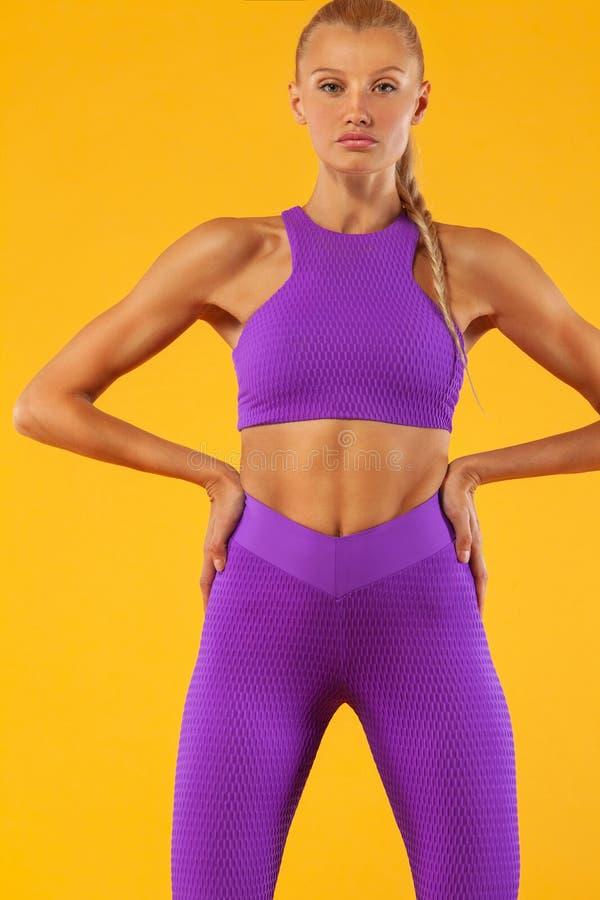 Konditionkvinnaidrottsman nen och kroppsbyggare Isolerat på gul bakgrund Sportcocnept royaltyfri fotografi