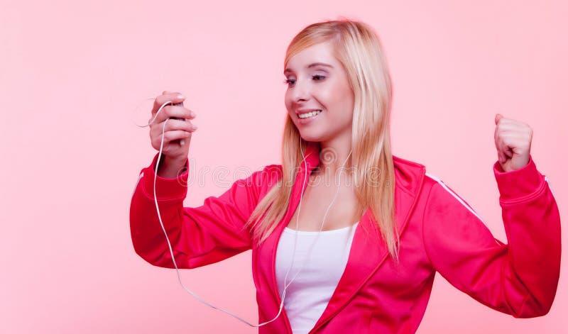 Konditionkvinnan lyssnar musik mp3 kopplar av idrottshall fotografering för bildbyråer
