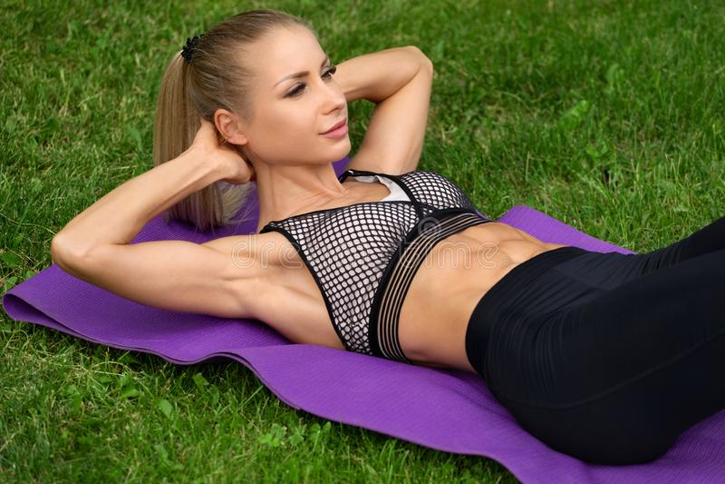 Konditionkvinnan som att göra sitter, ups det fria, genomkörare Sportigt öva för flicka som är buk-, utomhus- royaltyfri bild