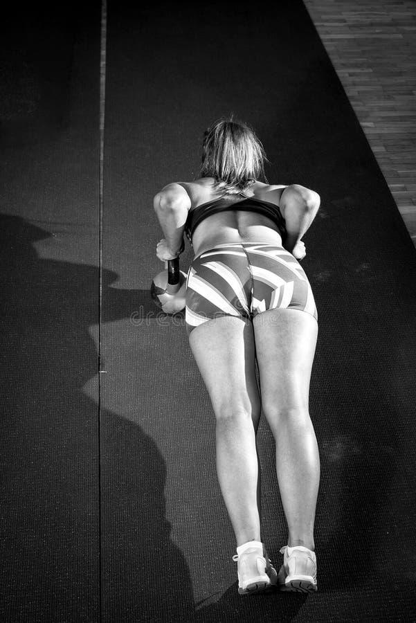 Konditionkvinnan som att göra skjuter, ups med kettlebells arkivbilder