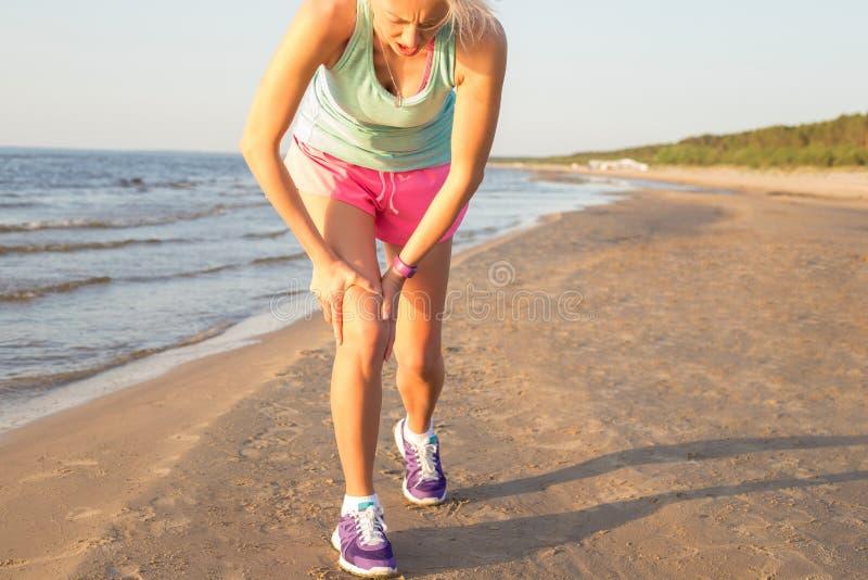 Konditionkvinnan som den har, smärtar i hennes knä royaltyfria foton