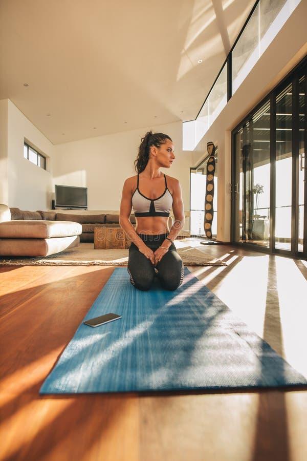 Konditionkvinnan som sitter Vajrasana yoga, poserar arkivfoto